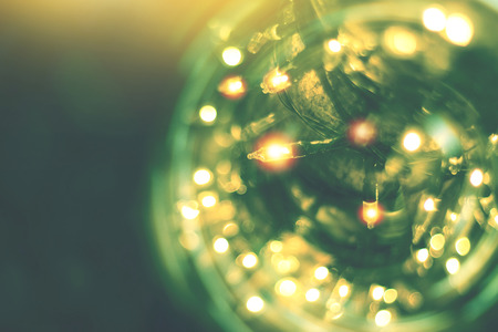 yellow string lights with bokeh decor in outdoor restaurant, blurred light bokeh with tree background