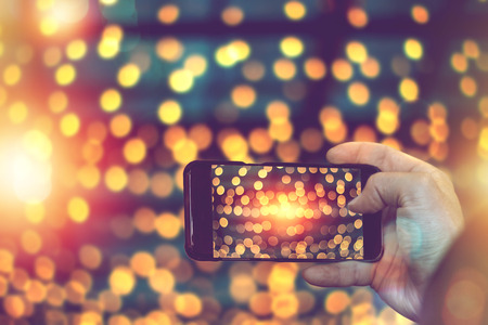 hand holding smart phone to taking photo of lighting decorate in festival.