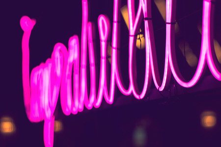 abstract pink neon sign with blurred neon tube light background, entertainment sign