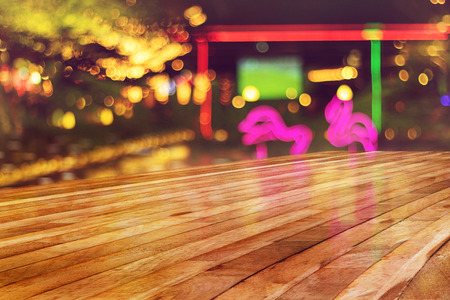 top of empty wood table with blur light of nightclub background