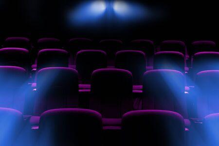 Cine vacío con asientos de color púrpura con rayos de luz de bengala del proyector Foto de archivo