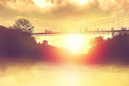 silhouette of tourist on suspension bridge walkway to the jungle in Surat Thani provine Thailand. Banco de Imagens