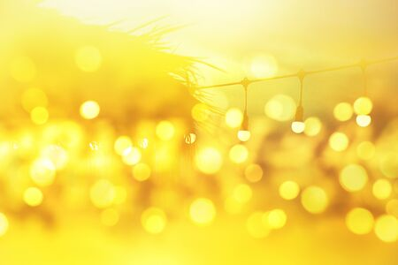 blurred light bokeh background on sunset, yellow string lights in outdoor restaurant, abstract background Banco de Imagens
