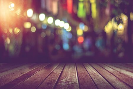 empty wooden table in front of abstract blurred night light bokeh in restaurant background Standard-Bild