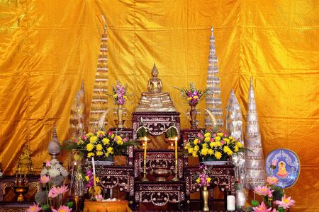 buddha images on the altar table in Thai religious ceremonies with yellow background