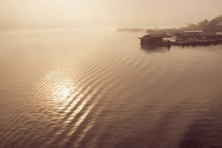 blurred scene of raft Huts on a river in the morning fog at Sangkhlaburi, Kanchanauri province, Thailand. travel in Thailand nature.