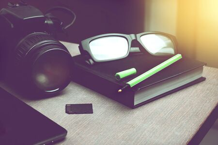 light green pen on black notebook organizer, smart phone and digital camera with memory card on wooden table. freelancer traveler photographer note. Standard-Bild