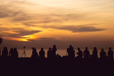 silhouette group of people sitting look at sunset light with orange sky at Phuket, Thailand