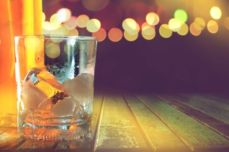 empty glass with ice cube on wooden table in local beach bar in Thailand with copy space