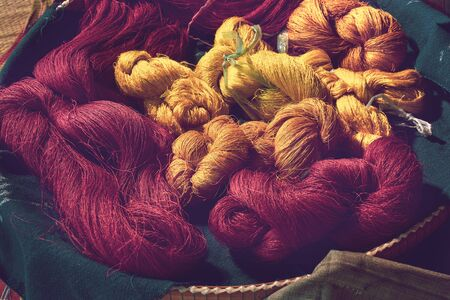 close up of red and yellow colour tie dye silk yarn for weaving, Thai mudmee fabric, silk yarn dyed from natural materials Stok Fotoğraf - 137890929