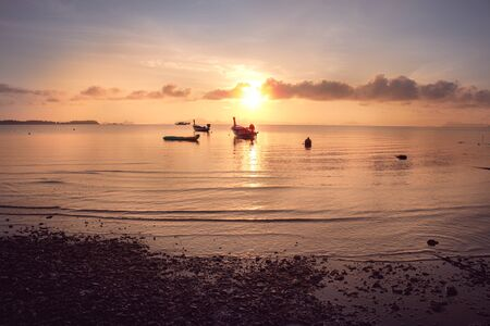 small motor fishing boat of the island villagers for tourists mooring along at the beach in sunrise, South of Thailand
