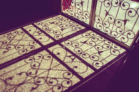 pattern of light and shadow on floor from asian style bending steel door in Thai temple.