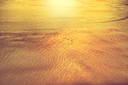 reflection of golden color sea wave on sand in sunset light at the beach Standard-Bild