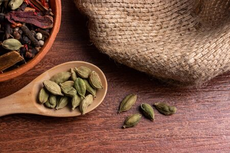close-up of dried cardamom pods in spoon on wood background, indian spice for cooking Standard-Bild
