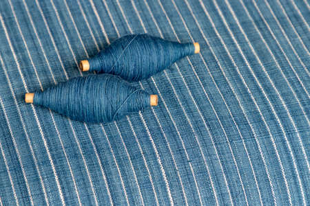 Indigo dyed yarn in reel and indigo dyed woven fabric background 版權商用圖片