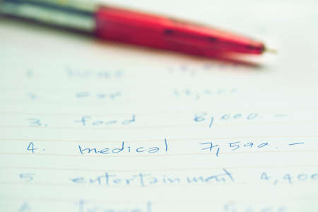 pen on white sheet with month budget for medical cost or to the treatment of illness