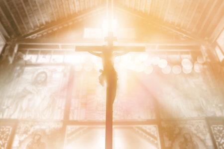 silhouette Jesus Christ crucifixion on cross over orange sunset light inside church background, prayer and praise religion concept