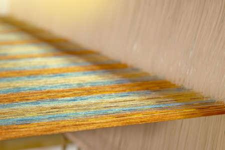 closeup of multicolour yarn on loom, abstract fabric weaving background Standard-Bild