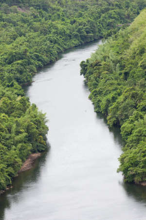 The river flows from the dam into the community  Stock Photo