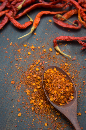 ground red chili peppers and allspice on a wood