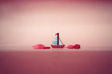 brighton: The tiny read sailboat on pink background Stock Photo