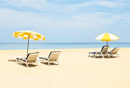 Pair of sun loungers and a beach umbrellas on the beach Stock Photo