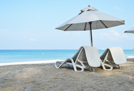 view of  Pair of sun loungers and a beach umbrella on the beach Stock Photo