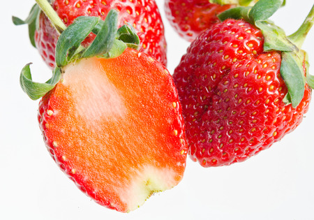 The strawberries are a bright red color with green stems and leaves. The fruit are in a good condition with details of small yellow seeds on each strawberry. The strawberries are piled on top of one another. Stock Photo