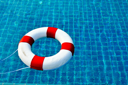Safety equipment, Life buoy or rescue buoy floating on swimming pool to rescue people from drowning man.
