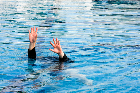 two hand of drowning man  in swimming pool  asking for help