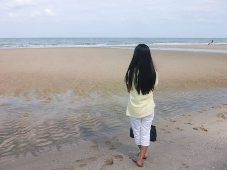 Woman stand looking at sea photo