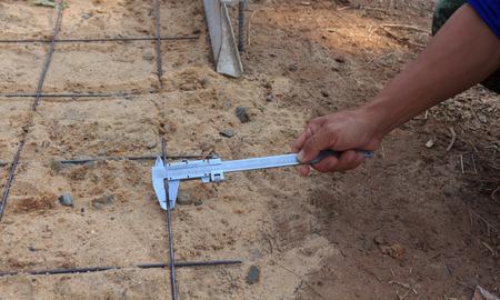 Workers using a verniercaliper measurement of rebar