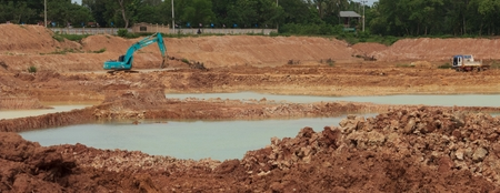Backhoere dredging the pond to store water for use during the dry season.Mahasarakham,Thailand,August 2016