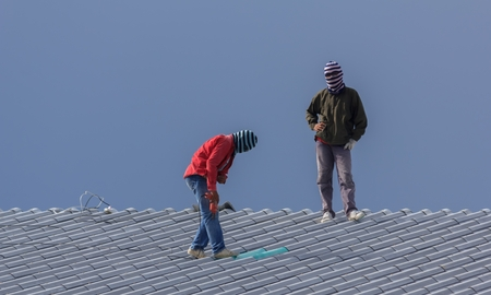 Workers are installing building roofs. Stock Photo