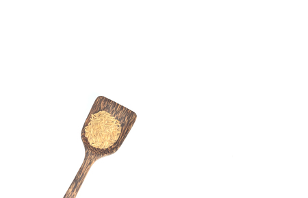 Grains in a wooden spoon on a white background.