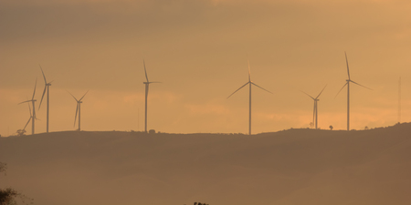industrial park: Wind turbines for electricity on a mountain at sunset. Stock Photo