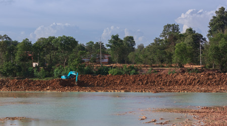 Backhoe dredging the pond to store water for public use in the dry season.Mahasarakham,Thailand,August 2016
