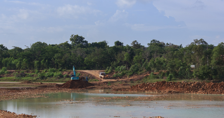dredging: Backhoe dredging the pond to store water for public use in the dry season.Mahasarakham,Thailand,August 2016