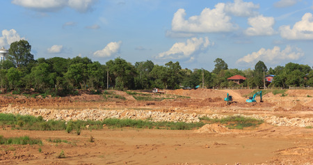 Backhoe dredging the pond to store water for public use in the dry season.Mahasarakham,Thailand,July 2016