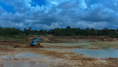 dredging: Backhoere dredging the pond to store water for use during the dry season.Mahasarakham,Thailand,August 2016