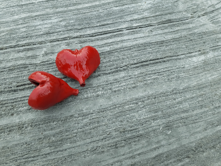 Two red hearts on the concrete floor. Stock Photo
