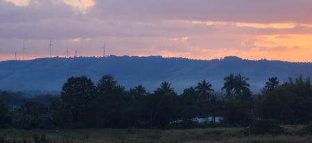 Wind turbines and beautiful sunset behind mountain. Stock Photo