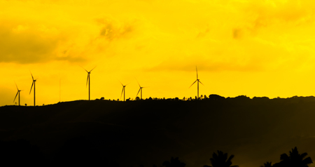 Wind turbines for electricity on a mountain at sunset. Stock Photo