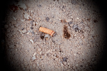 Cigarette butts in the sand. Stock Photo