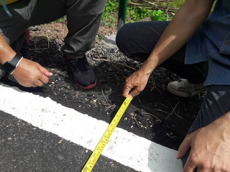 Technician measuring the width of the road Banque d'images