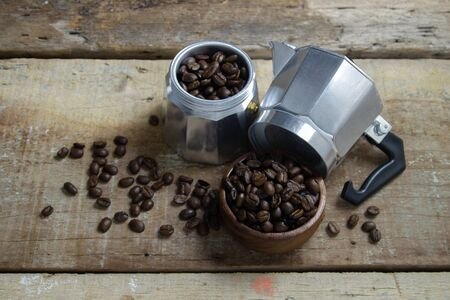 Moka pot with coffee bean on a Grunge Wooden background