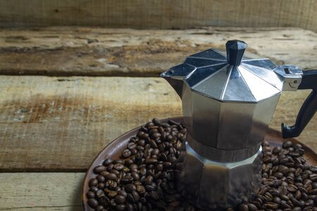 Roasted Coffee beans with Moka pot on grunge wooden can be used as a background