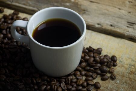 Coffee beans and espresso on wood background