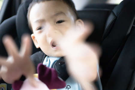 1 Year Old Adorable, an Asian Toddler Boy, Sitting in a Car Seat on a Car While Traveling Looking at the camera. Family Trips and Baby Care and Safety Concept. Front View Closeup Blurry Background.