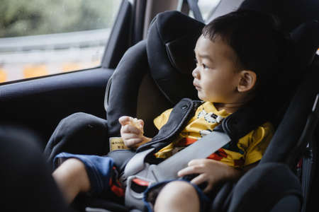 1 Year Old Adorable Asian Boy Alone Looking Around From Car Seat in the Car Portrait. Family Trips and Baby Care and Safety Concept. Front View Headshot CloseUp Copy Space, and Blurry Background. Stockfoto